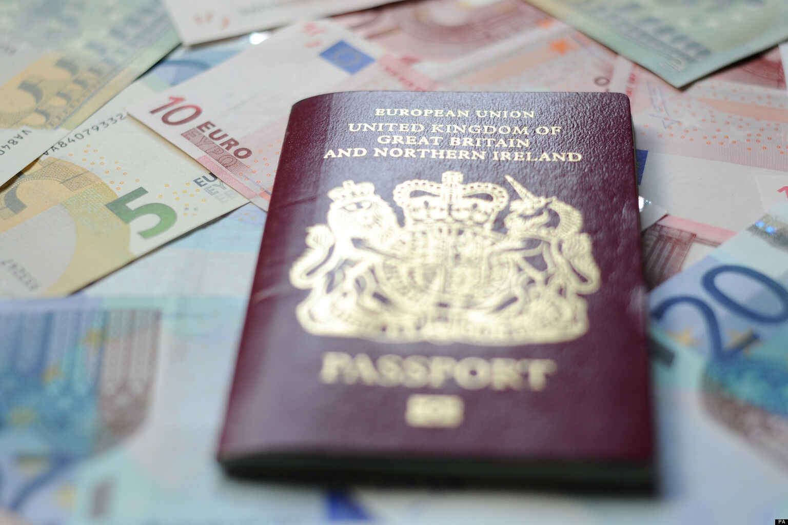 A British passport sits on top of Euro bank notes